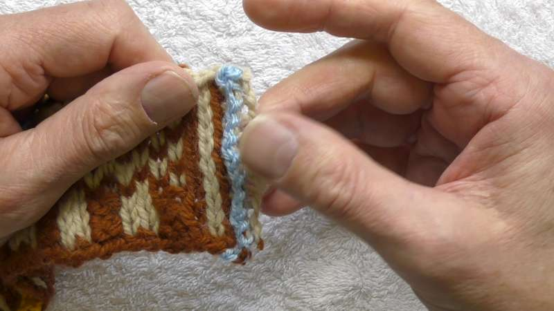 The cut ends of the steek stitches.