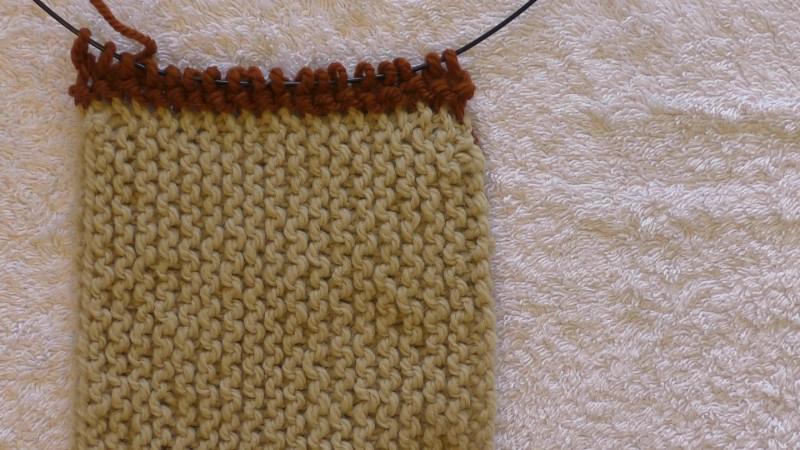 New (dark coloured) fabric knit onto the edge of the original (light coloured) fabric.
