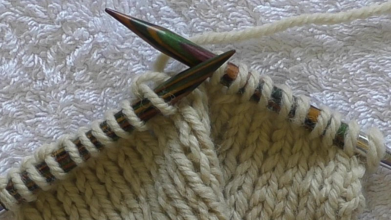 Stocking stitch swatch with half the final row completed. The working yarn is attached to the stitches on the left hand needle with the next stitch to be knit on the right hand needle.