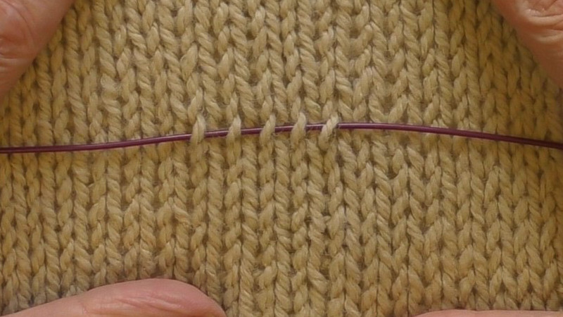 Swatch in stockinette stitch with the cable of an interchangeable needle passing under the right hand leg of five stitches. These five stitches will be picked up to create a new fabric.