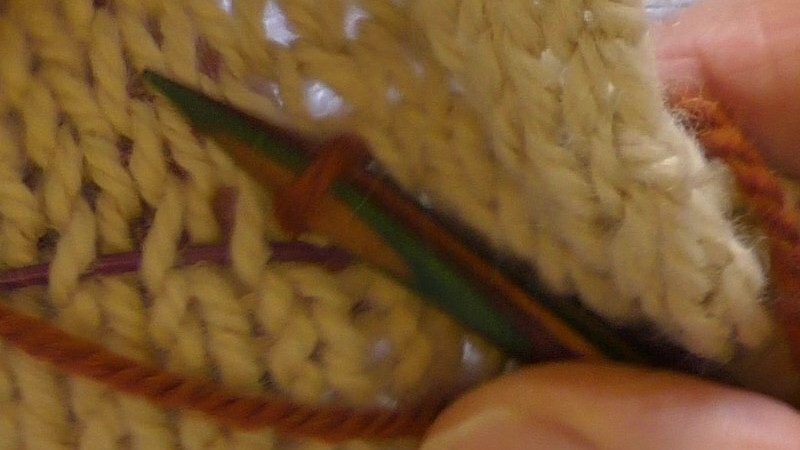 Loop of yarn around a needle on the public (right) side of the fabric.The end of the working yarn that is still attached to the ball can be seen lying across the fabric.