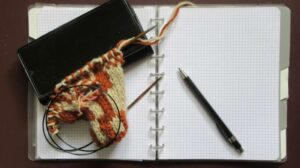 Notebook under knitted work in progress, mobile phone and a pencil.