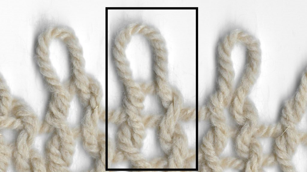 """Rows of loosely knit knit stitches. The central column is highlighted to show how the characteristic """"V"""" of a knit stitch is formed."""