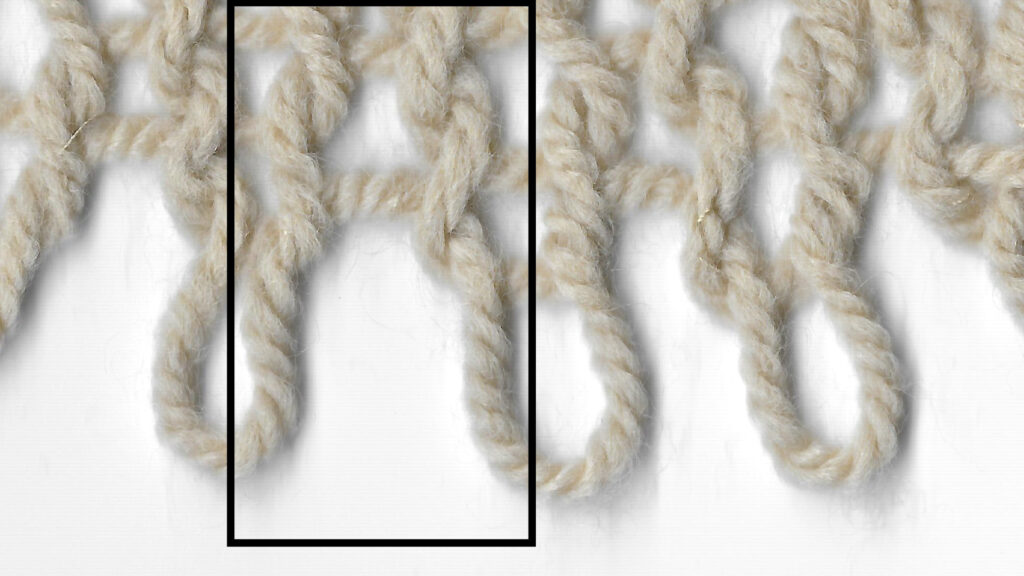 """An area of knit stitches shown with the live stitches at the bottom of the image and the cast-on edge at the top. A column of """"spaces"""" between stitches is highlighted."""