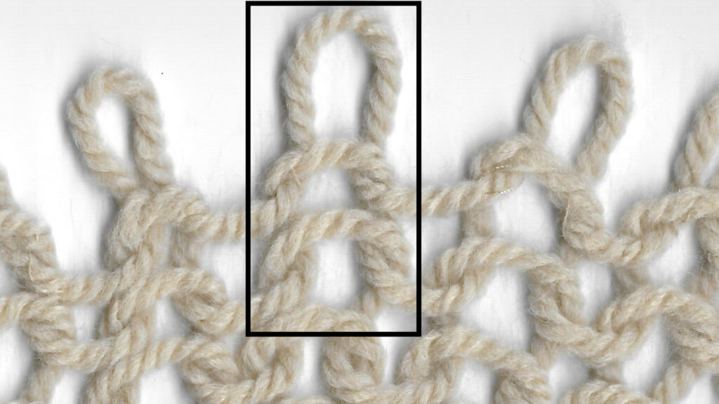 Area of knitting showing purl stitches. One column of stitches is highlighted.