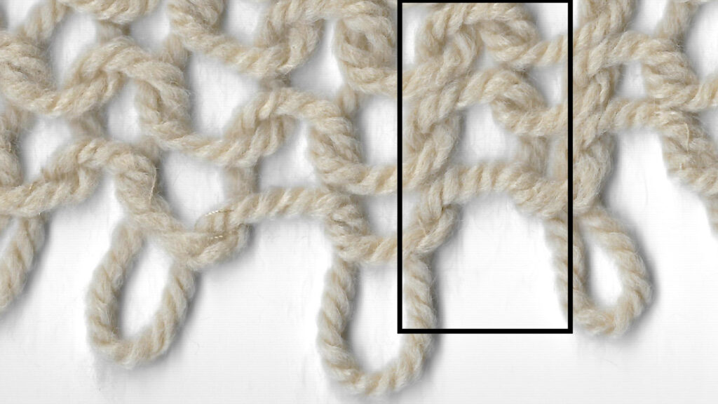 """An area of purl stitches shown with the cast-on edge at the top of the picture. A column of the """"gaps"""" between stitches is highlighted."""